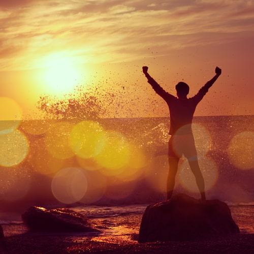 A man celebrating sobriety on the beach.