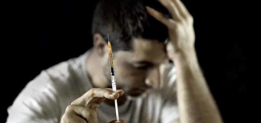 A man holding a syringe of heroin.