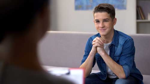 A teenage male sitting in a substance abuse meeting.