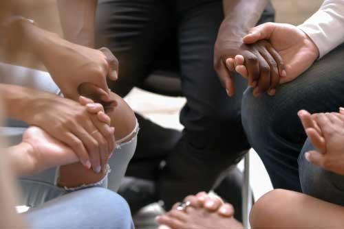 A group of people, sitting in a circle, holding hands.