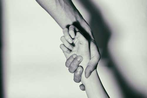 Two people, one hand holding on to another persons wrist.